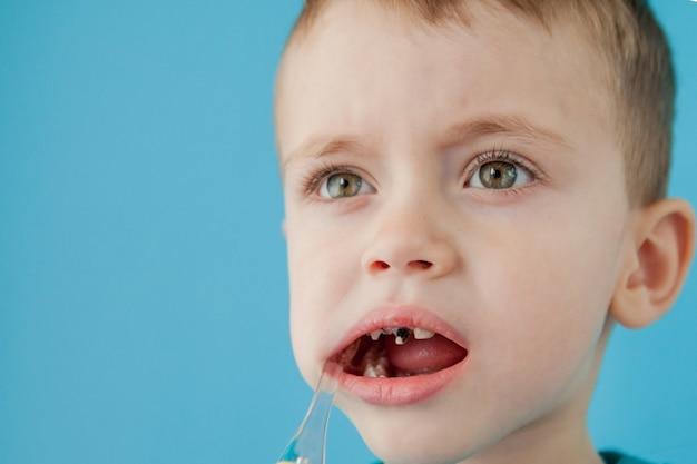 Kleine schattige jongen zijn tanden poetsen op blauwe muur