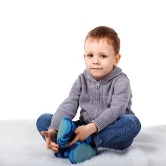 Kleine schattige jongen zittend op de vloer haar onderlip bijten op wit wordt geïsoleerd