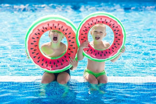 Kleine schattige kinderen bij het zwembad. kinderen hebben plezier in de zomer.