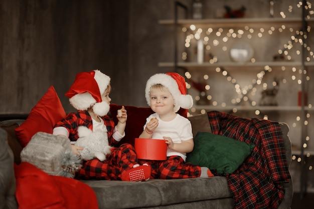 Kleine schattige kinderen in kerstmutsen zittend op een grote gezellige stoel in de kamer met kerstcadeautjes doos
