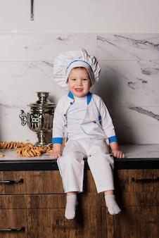 Kleine schattige kok met bestek zittend op een keuken, tweelingbroers, mandarijn, bagels