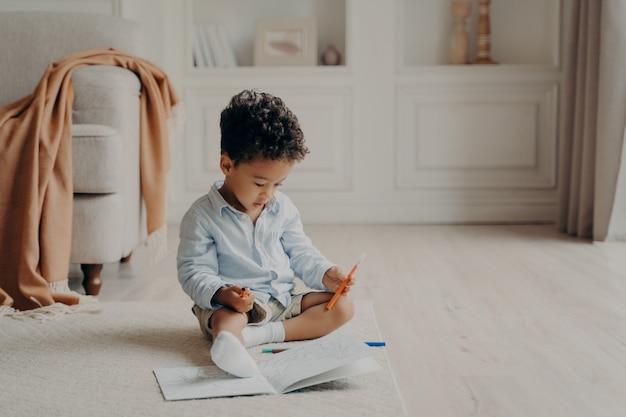 Kleine schattige krullende mulat jongen zittend op de vloer in de woonkamer voor kleurboek met viltstift in de hand, kind beslissen welke superheld te kleuren terwijl hij vrije tijd thuis doorbrengt