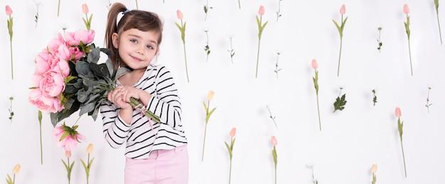 Kleine schattige meisje bedrijf rozen