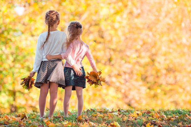 Kleine schattige meisjes buiten op warme zonnige herfstdag