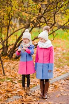 Kleine schattige meisjes buitenshuis op warme zonnige herfstdag