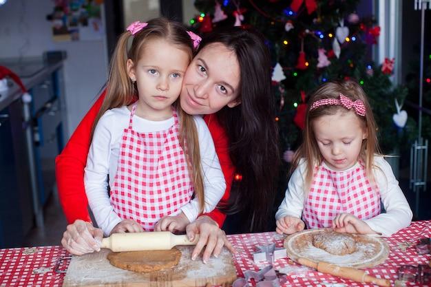 Kleine schattige meisjes en jonge moeder kerstkoekjes peperkoek bakken