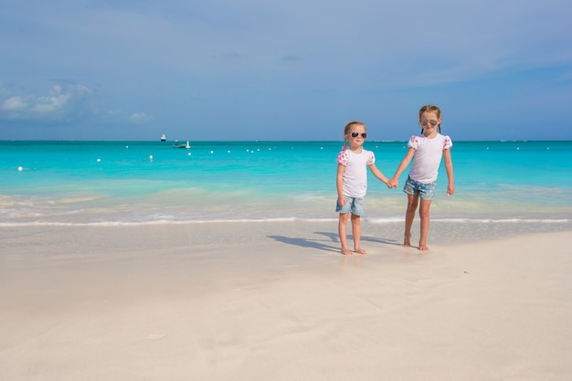 Kleine schattige meisjes genieten van hun zomervakantie op het strand