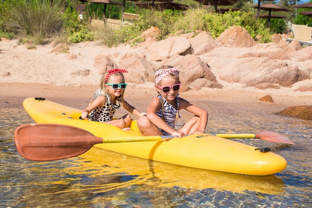 Kleine schattige meisjes genieten van kajakken in het heldere turquoise water