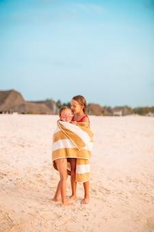 Kleine schattige meisjes gewikkeld in een handdoek op tropisch strand. kinderen op het strand vakantie