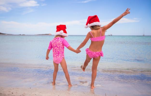Kleine schattige meisjes in kerstman hoeden tijdens strandvakantie