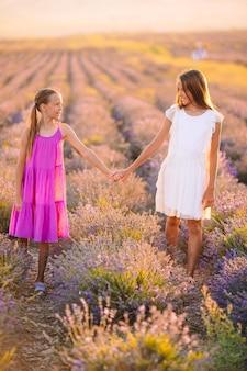 Kleine schattige meisjes in lavendel bloemen veld in witte jurken genieten van zomervakantie