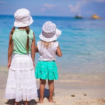 Kleine schattige meisjes in mooie jurk op wit strand