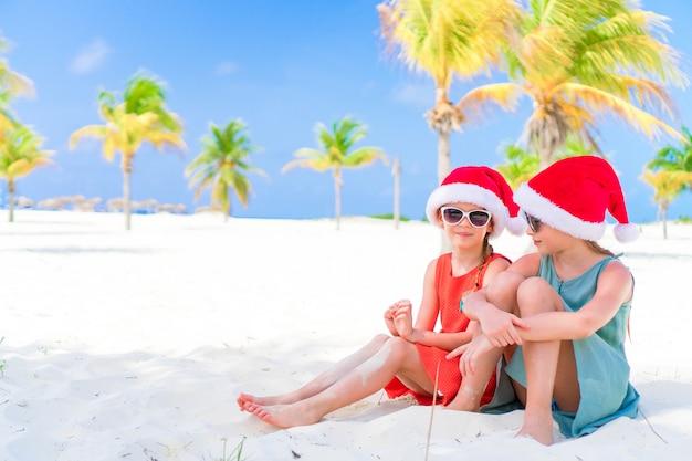Kleine schattige meisjes in santa hoeden tijdens strandvakantie hebben plezier samen