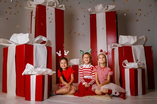 Kleine schattige meisjes in studio met wintervakantie decoratie en rekwisieten.