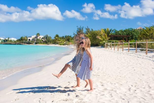 Kleine schattige meisjes lopen langs het witte strand en plezier maken