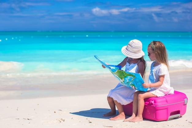 Kleine schattige meisjes met grote koffer en een kaart op tropisch strand