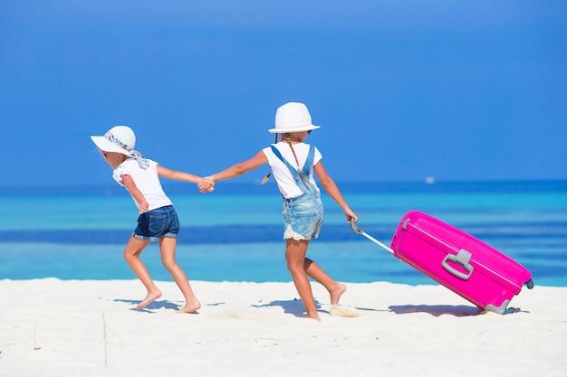 Kleine schattige meisjes met grote koffer op tropisch wit strand tijdens de zomervakantie