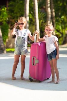 Kleine schattige meisjes met grote koffer op tropisch wit strand tijdens zomervakantie