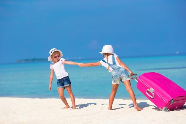 Kleine schattige meisjes met grote koffer op tropisch wit strand