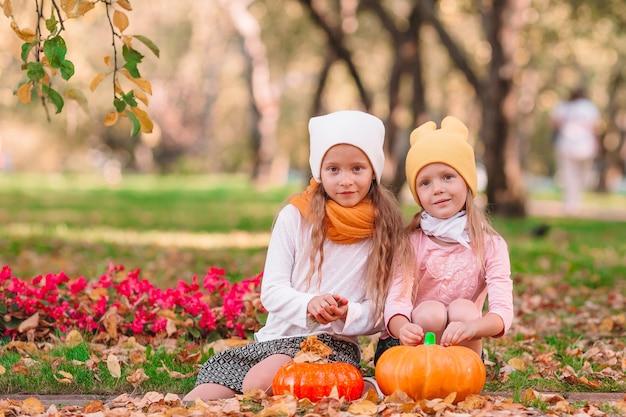 Kleine schattige meisjes met pompoen buiten op een warme herfstdag. portret van kinderen in de herfst op oktober