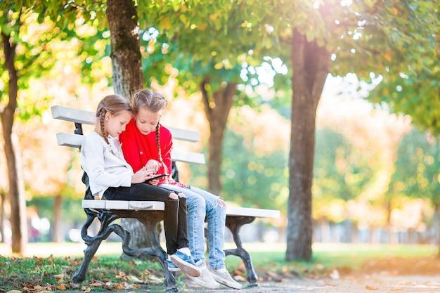 Kleine schattige meisjes met smartphone in de herfst buitenshuis. kinderen plezier op warme zonnige dag in de herfst park