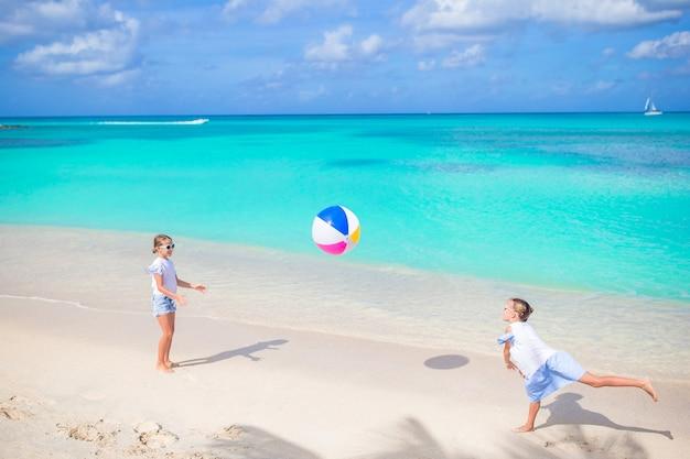 Kleine schattige meisjes spelen met de bal op het strand. kinderen plezier aan de kust
