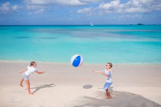 Kleine schattige meisjes spelen met de bal op het strand