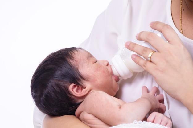 Kleine schattige pasgeboren baby consumptiemelk uit fles kijken naar haar moeder
