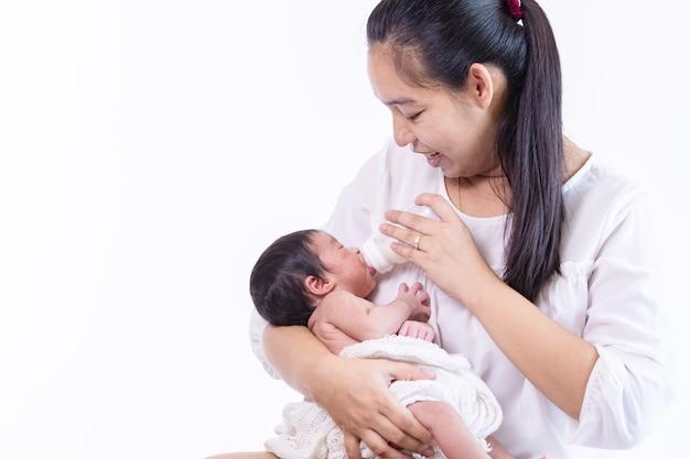 Kleine schattige pasgeboren baby consumptiemelk uit fles kijken naar haar mooie moeder