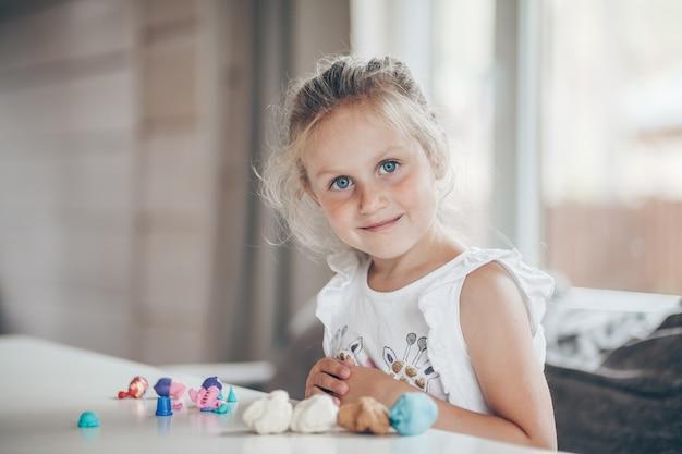 Kleine schattige peuter kind meisje educatieve spelletjes spelen met plasticine cijfers school voorbereiden
