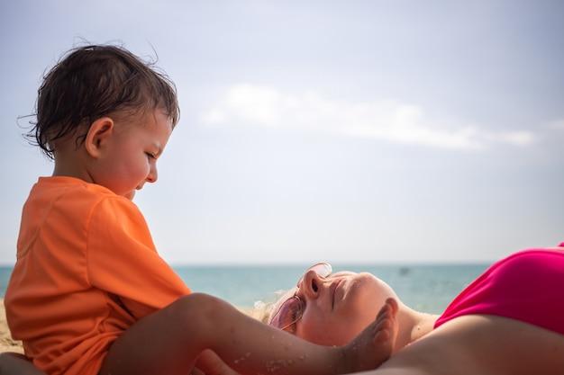 Kleine schattige peuter zit op het strand in de buurt van moeder die op het zand ligt. warme zee op een zonnige dag op de achtergrond