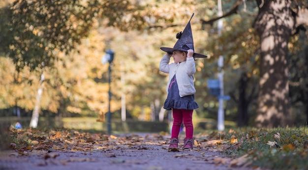 Kleine schattige peuterheks met een hoed staat in een herfstpark op zonnige dag halloween