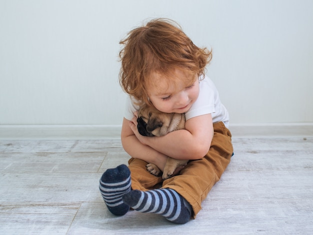 Kleine schattige roodharige krullende jongen in wit t-shirt met zijn pug puppy
