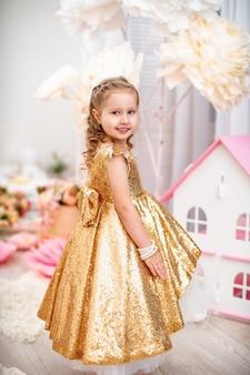 Kleine schattige vrouw van 4 jaar oud met krullend haar en een gouden jurk