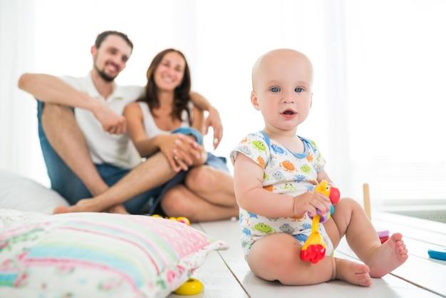 Kleine schattige zes maanden oude baby spelen met speelgoed