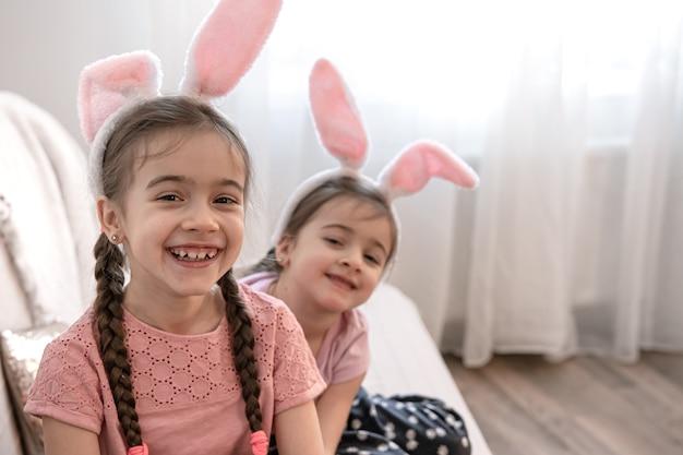 Kleine schattige zusjes in konijnenoren close-up