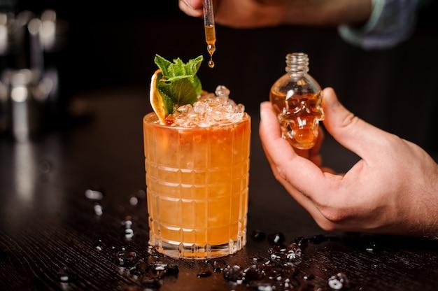 Kleine schedelvormige fles, oranje cocktail en barmannenhand