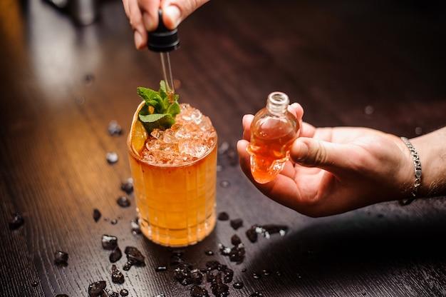 Kleine schedelvormige fles, zomercocktail en barmannenhand