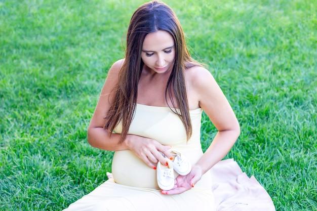 Kleine schoentjes voor de ongeboren baby in de buik van een zwangere vrouw