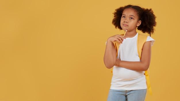 Kleine school meisje kopie ruimte gele achtergrond
