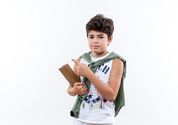 Kleine schooljongen met boek en wijst naar de zijkant