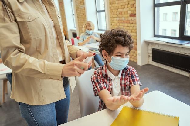 Kleine schooljongen met een beschermend masker klaar voor het schoonmaken van zijn handen, vrouwelijke leraar met behulp van een