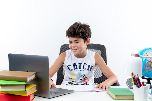 Kleine schooljongen zittend aan een bureau met school tools gebruikte laptop geïsoleerd op wit