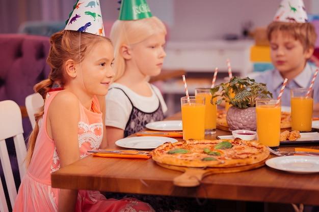 Kleine schoonheden. blij blond meisje positiviteit uiten terwijl het dragen van papieren hoed