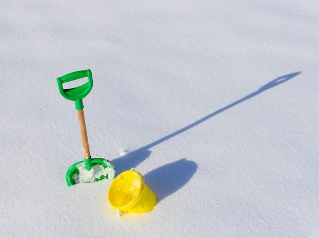 Kleine schop en emmer in diepe sneeuw