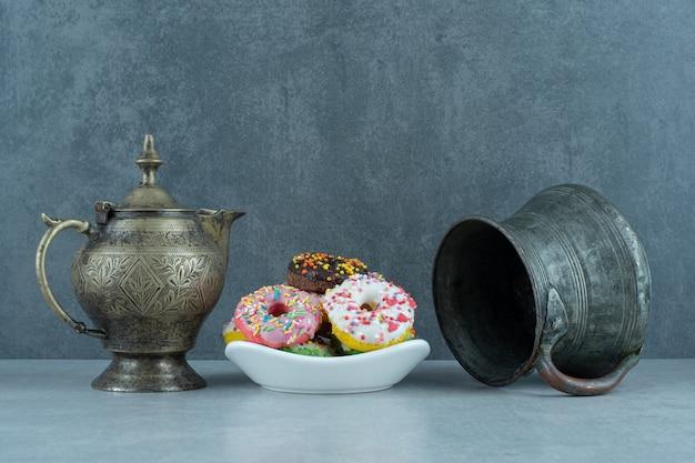 Kleine schotel met donuts tussen een theepot en een kan op marmer.