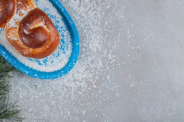 Kleine schotel met een zoet broodje op marmeren tafel.