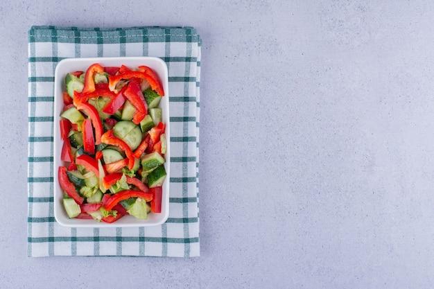 Kleine schotel van gemengde groentesalade op een verteld tafelkleed op marmeren achtergrond. hoge kwaliteit foto