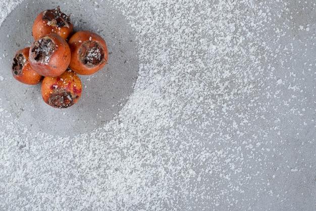 Kleine schotel van kaki's op verspreide kokospoeder op marmeren tafel.
