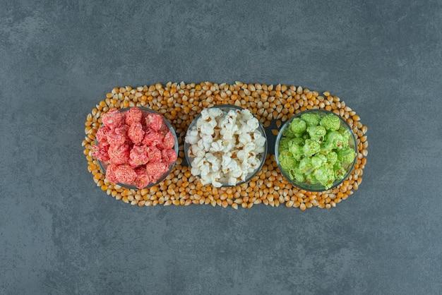 Kleine serveerschalen met diverse popcorn omgeven door maïskorrels op marmeren achtergrond. hoge kwaliteit foto